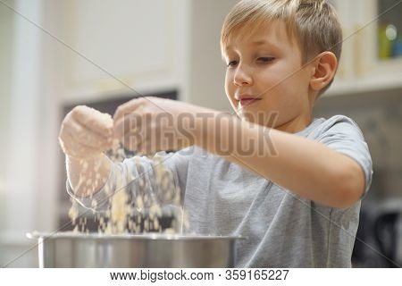 Child cooking at the kitchen. White boy stirring dough for a cookie. Kid is mixing ingredients for a cake in the steel bowl. 8 years old child cooking food at home.