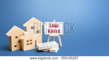 Figurines Of Houses And An Easel With Low Rates. Low Demand For Real Estate And Housing, Economic Do