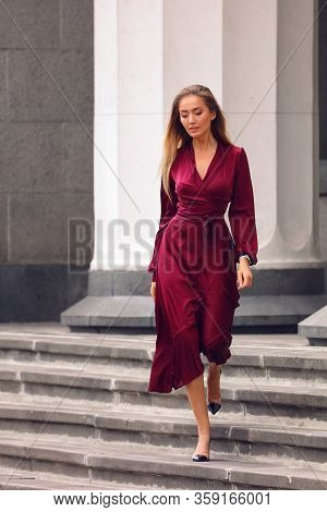 Sexy Business Lady Walking Down The Steps On High Heel Shoes. Elegant Burgundy Dress With Long Sleev