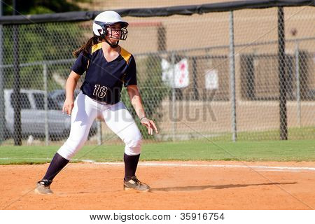 Young teen girl playing softball in organized game