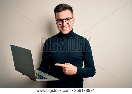 Young handsome caucasian business man wearing glasses using computer laptop very happy pointing with hand and finger