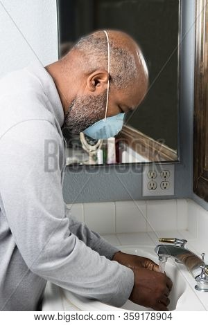 Corona Virus protection with African American man washing hands with mask. Concept of Lockdown, Flatten the Curve, Social Distancing, State of Emergency