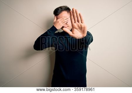 Young handsome caucasian man wearing glasses and casual sweater over isolated background covering eyes with hands and doing stop gesture with sad and fear expression. Embarrassed and negative concept.