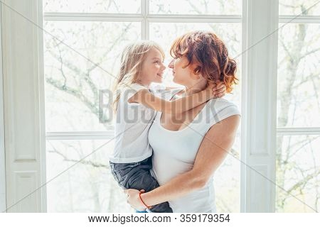 Stay Home Stay Safe. Young Mother Holding Her Child. Woman And Little Girl Relaxing In White Bedroom