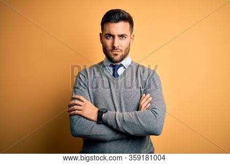 Young handsome businessman wearing elegant sweater and tie over yellow background skeptic and nervous, disapproving expression on face with crossed arms. Negative person.