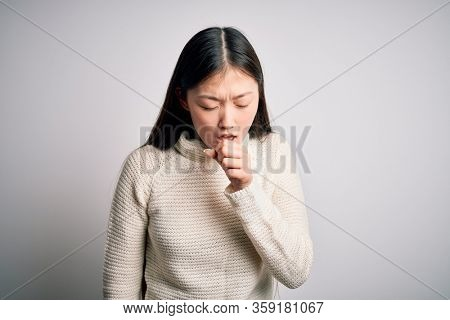 Young beautiful asian woman wearing casual sweater standing over isolated background feeling unwell and coughing as symptom for cold or bronchitis. Health care concept.