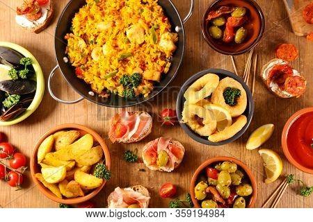 assorted of spanish food- tapas, paella, potato bravas, mussels