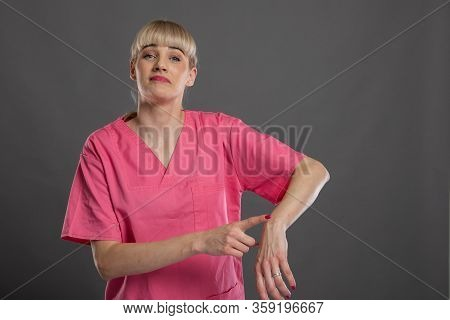 Portrait Of Young Attractive Female Nurse Making Late Gesture