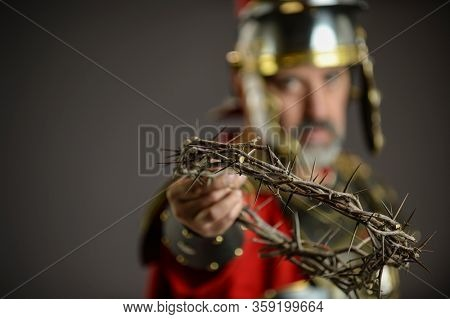 Roman soldier holding a crown of thorns isolated on a dark background