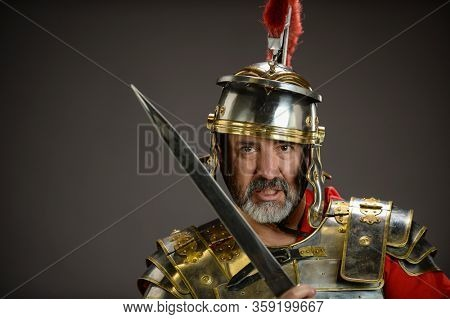 Portrait of a Roman Soldier holding his sword isolated on a dark background