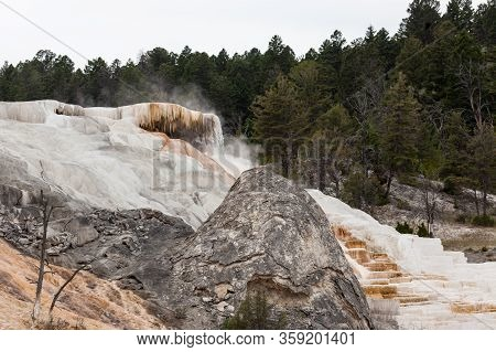 An Old Grey Dormant Hot Springs Cone Next To A Vibrant White Active Travertine Flow Terracing Down A