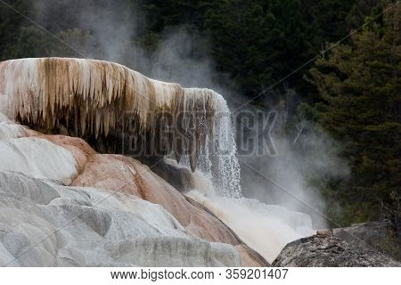 Hot Water Cascades Off Of A Travertine Feature With Stalactites Hanging Down And Hot Steam Floating