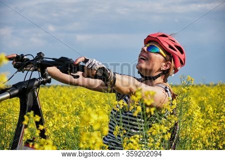 Female Cyclist Tilting Back Her Bicycle In A Rapeseed Field.
