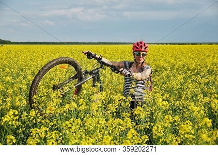 Woman Lifting Her Bicycle On The Rear Wheel, In A Rapeseed Filed, On A Sunny Day.