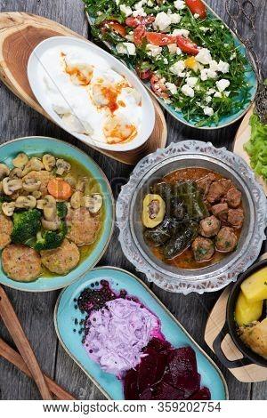 Eid Mubarak Traditional Ramadan Iftar dinner. Assorted tasty food in authentic rustic dishes on wooden blue background.  Turkish Bosnian food meat kebab, pita, Sarma.