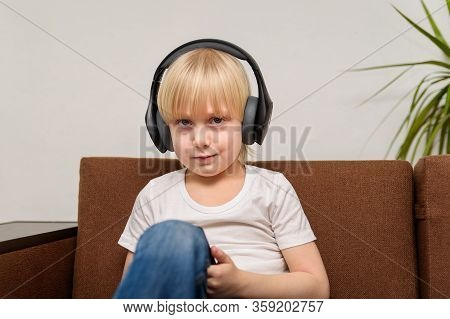 Fair Hair Boy In Headphones Sitting On Couch. Teenager Listening To Music.