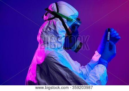 Coronavirus, Doctor holding positive covid-19 virus Blood Sample test tube. Wearing biohazard epidemic Protective mask, suit and glows neon light background