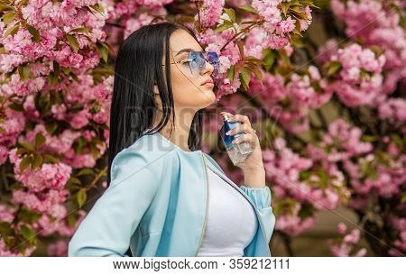 Cherry Blossom Aroma. Fashionable Woman Hold Perfume Bottle. Female Perfume. Spring Perfume. Fancy S