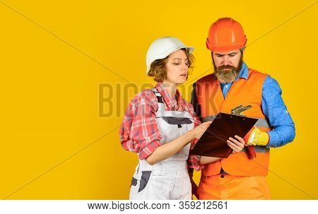Family Counting Finances For Renovation. Woman And Man Wear Safety Hard Hat. Redevelopment Of Home.