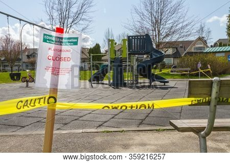 A Covid-19 Closed Playground Sign Caution Taped To A Park Bench With Plaground In Background