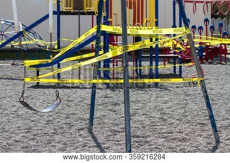 A Single Swing Is Caution Taped Off On A Playground Swing Set During Covid-19 Pandemic.