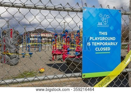 Playground Is Temporarily Closed Sign On Chain Link Fence With Playground In Background