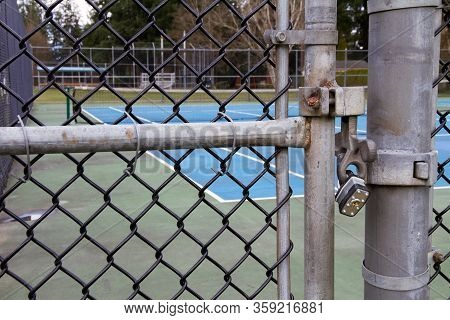 The Gate Of A Tennis Court Is Padlocked Shut With Tennis Net In Background.