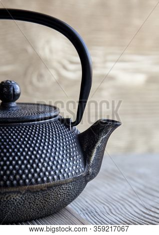 Part Of Black Metall Tea Pot On A Wooden Background