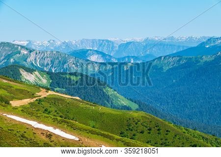 Green Mountain Ridges, Surrounded By High Mountains. Dirt Road On A Mountain Range. Snow-capped Moun