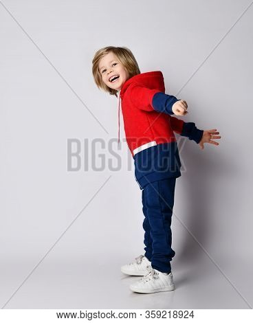 Full Growth Portrait Of Frolic Laughing Blond Kid Boy In Red And Blue Sport Suit Standing Sideways T