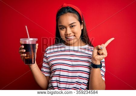 Young asian girl drinking cola fizzy refreshment using straw over isolated red background very happy pointing with hand and finger to the side