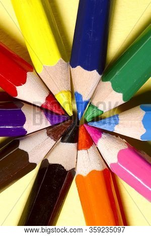 Many Colored Pencils On A Yellow Background. Colored Pencils Folded In A Circle. Top View, Macro, Ve