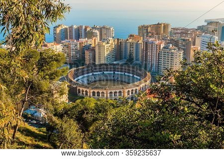 View Of The Bullring On The Spanish Coast In Malaga. In The Middle Between High-rise Buildings With