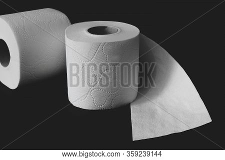 Unwrapped White Toilet Paper Rolls On Black Matte Background With Copy Space