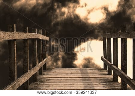 The End Of A Wooden Bridge Leading Towards A Drop. Billowing Dark Smoky Clouds And Glowing Light Giv