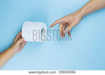 Female Hand Gives Toilet Paper Roll To Male Hand On Blue Background, Top View, Flat Lay. Panic Buyin