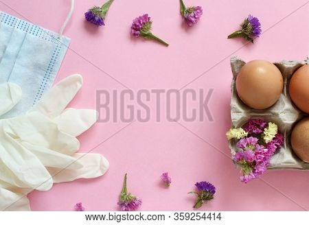 Gloves, Facemask, Flowers And Eggs Over Light Pink Background Top View. Easter During Coronavirus Co