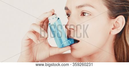 Young Woman Using Inhaler During Asthmatic Attack At Home, Closeup, White Background