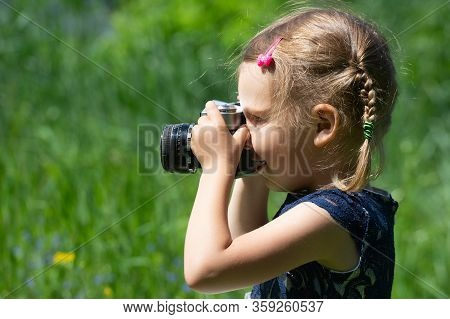 A Little Girl Takes A Picture With A Retro Film Camera In The Summer In The Park. Little Pretty Chil