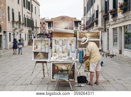 Venice, Italy - June 30, 2017: A Male Street Artist Is Hanging A Picture In His Stall In Venice, Ita