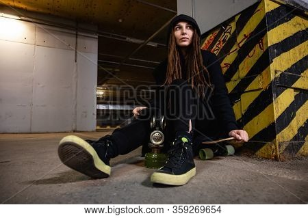 Girl With Dreadlocks In Black Clothes Sits In An Underground Parking Lot With A Gas Mask