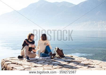 Picnic At Winter Sea Beach. Couple In Love Drink Coffee. Young Travelers Sitting Outdoors. Happy Man