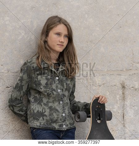 Horizontal Portrait Of Young Girl With Skateboard