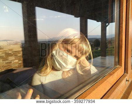 little girl in medical mask sitting near the window at home quarantine coronavirus covid-19