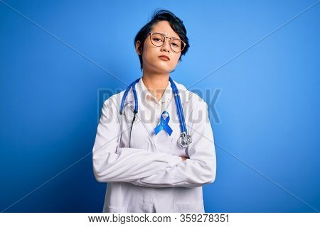 Young beautiful asian doctor girl wearing stethoscope and coat with blue cancer ribbon skeptic and nervous, disapproving expression on face with crossed arms. Negative person.