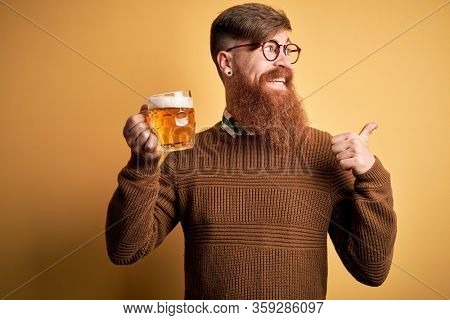 Irish redhead man with beard drinking a glass of refreshing beer over yellow background pointing and showing with thumb up to the side with happy face smiling