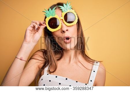 Young beautiful brunette woman wearing pineapple sunglasses over yellow background scared in shock with a surprise face, afraid and excited with fear expression