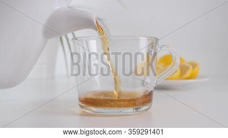 Pour Hot Tea On Glass Cup. White Teapot. Slow Motion.