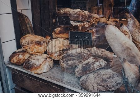 Variety Of Fresh Artisan Loaves Of Bread On A Window Display Of A Bakery, Selective Focus.