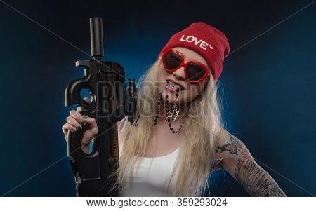 A Bright Blonde In A Red Hat With A Submachine Gun On A Dark Background